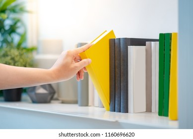 Male student hand choosing and picking off yellow handcover book from bookshelf in college library for education research. Bestseller collection in bookstore. Scholarship and educational opportunity