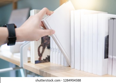 Male student hand choosing and picking off white handcover book from bookshelf in college library for education research. Bestseller collection in bookstore. Scholarship and educational opportunity