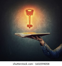 Male student hand holding an open book with a magic shining, golden key over a dark blackboard background. Symbol of unlimited access to knowledge and intelligence, educational concept, unlock wisdom.