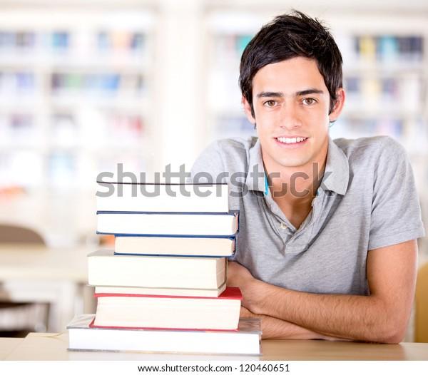 Männlicher Schüler in der Bibliothek mit einem Haufen Bücher