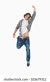 Male student posing by jumping with a raised arm against white background