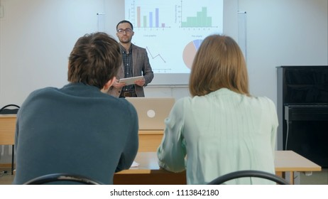 Male student raising hand and asking teacher a question sitting on table