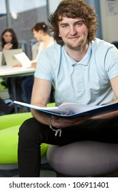 Male student sitting with folder at college with colleagues in the background