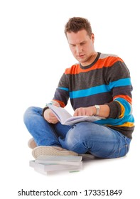 Male student sitting on floor, reading a book, preparing for exam, isolated on white background.