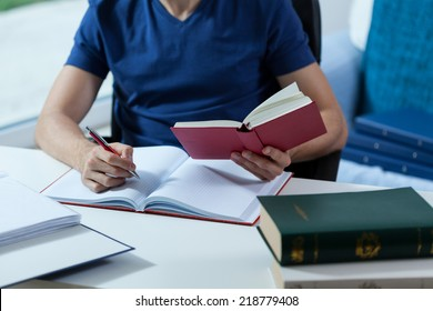 Male student transcribing the notes from the book in library