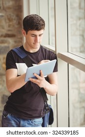 Male student using digital tablet while leaning on window in college
