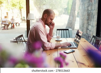 Male student work on computer touch pad while talking on smart phone, young business man use laptop sitting at wooden table of modern coffee shop, freelancer working on notebook at hipster loft space