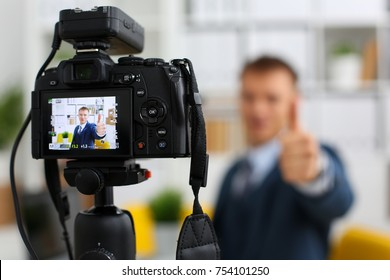 Male in suit and tie show confirm sign arm making promo videoblog or photo session in office camcorder to tripod closeup. Vlogger promotion selfie solution or finance advisor management information