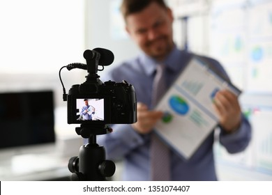 Male in suit and tie show stats graph pad making promo videoblog or photo in office camcorder to tripod portrait. Vlogger selfie solution or finance advisor management information professional concept
