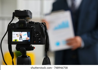 Male in suit and tie show stats graph pad making promo videoblog or photo session in office camcorder to tripod closeup. Vlogger selfie sale solution or finance advisor management information