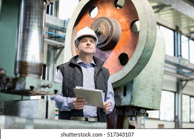 Male supervisor holding clipboard in metal industry
