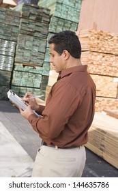 Male supervisor stock taking in warehouse