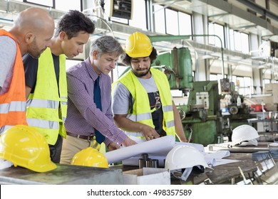 Male supervisor with workers discussing over blueprints in industry