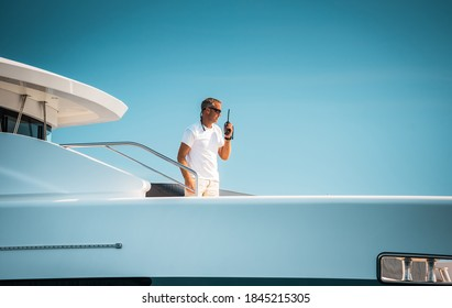 Male superyacht Deckhand with a handheld radio getting ready to drop anchor, with a blue sky in the background