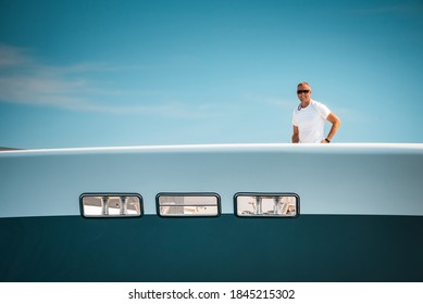 Male Superyacht Deckhand smiling while getting ready to drop anchor, with a blue sky in the background