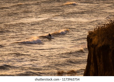 A male surfer catches a wave toward shore in a cold water bay as the sun sets.