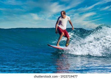 Male surfer on a blue wave at sunny day