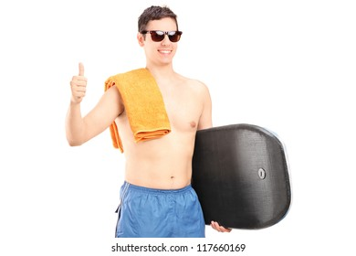A male surfer posing with surfboard and giving a thumb up isolated on white background