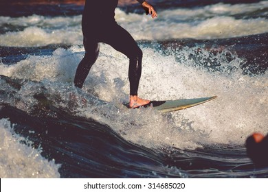 male surfer riding a wave on a white water river park with a retro vintage instagram filter