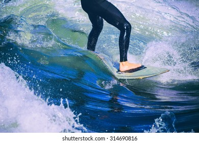 male surfer riding a wave on a white water river park with a retro toned instagram filter