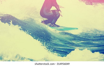 male surfer riding a wave on a white water river park with a toned vintage instagram filter