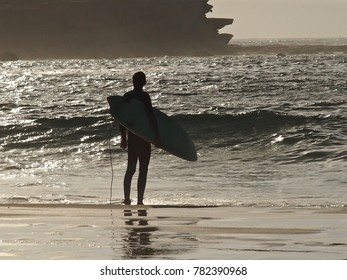 Male Surfer in Silhouette Contemplating the Brilliant Surf on Bondi Beach.