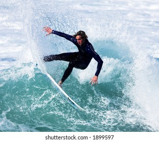 Male surfer slashes wave in cutback