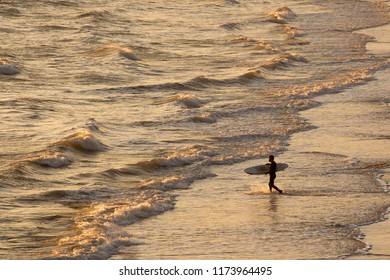 A male surfer walks into the surf in a  wetsuit as the sunset brings warmth to the sea.