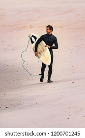 Male surfer wearing wetsuit, holding surfboard under his arm, walking on beach after morning surfing session.