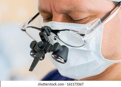 Male surgeon with binocular glasses