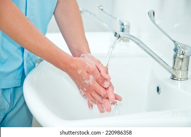 Male surgeon washes his hands before the operation