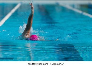 Male swimmer in an outdoor swimming pool, swim backstroke