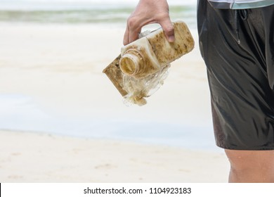 A male swimmer picking up dirty plastic garbage washed ashore onto tropical white sand beach. Beat plastic pollution concept. World Environment Day 2018.