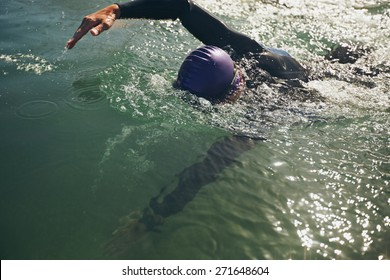 Male swimmer swimming in open water. Athlete practicing for the competition.