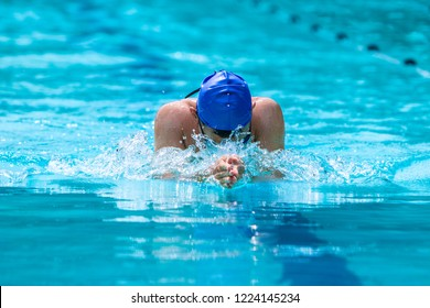 Male swimmer working on his breaststroke  swimming at a local pool on a bright sunny day