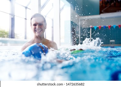 Male Swimming Coach Giving Boy Learning Backstroke One To One Lesson In Pool