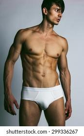 Male swimwear & underwear concept. Handsome muscular male model in trendy white underwear posing over grey background. Studio shot