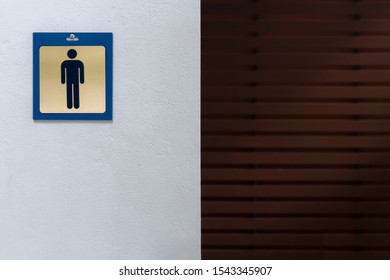 Male symbol contains in a blue plastic frame stick by screw nail head on rough white cement wall of public men toilet with blurred dark brown plank woods and sun lighting from clear roof background.