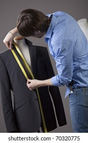 male tailor by the work on business jacket