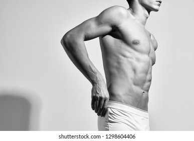 male tatlet with pumped naked body on gray isolated background sport fitnes