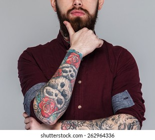 Male with tattoed hands and beard posing