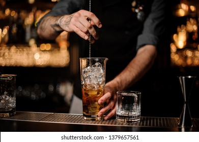 Male tattooed bartender in gray shirt stirring alcohol cocktail with special long bar spoon