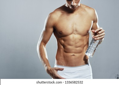 Male taurus muscular pumped body behind a bottle of water in his hands in white shorts on a gray background