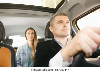 Male taxi driver and female passenger in car