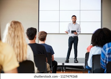 Male Teacher With Digital Tablet Giving Presentation To High School Class In Front Of Screen