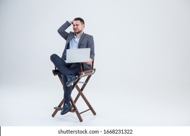 Male teacher director businessman sitting on a chair studying documents. He is looking at the laptop screen. New business project.