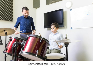 Male teacher guiding little boy in drum learning tutorial at music academy