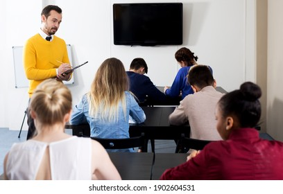 Male teacher inspecting working process of students during exam in class