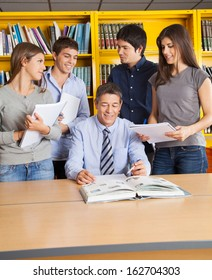 Male teacher sitting at table while students standing around him in university library