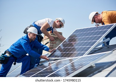 Male team engineers installing stand-alone solar photovoltaic panel system. Electricians mounting blue solar module on roof of modern house. Alternative energy concept.